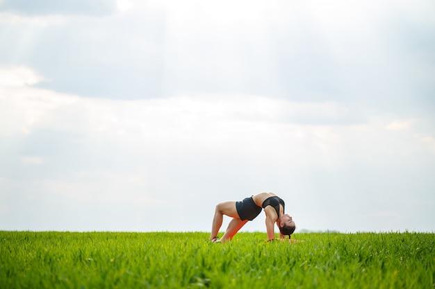 Flexibles mädchen, akrobat, gymnastikbrücke, handstand, anmutige frau. führt in der natur schöne posen für flexibilität durch, ein sportmodell auf blauem himmelshintergrund.