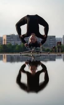 Flexibles mädchen, das sich mit spiegelung im wasser kopfüber biegt. individualität, kreativitätskonzept