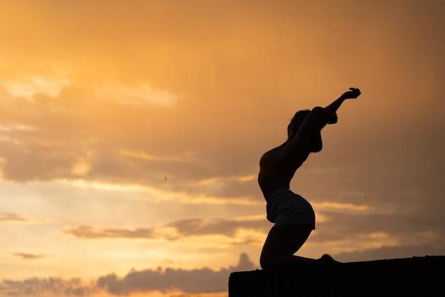 Flexibles mädchen, das übung auf himmelhintergrund während des dramatischen sonnenuntergangs tut