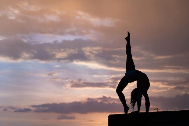 Flexibles mädchen, das während des dramatischen sonnenuntergangs übung auf himmelshintergrund macht