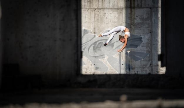 Flexibles und fittes mädchen, das auf ihren händen steht und das gleichgewicht im verlassenen gebäude hält. konzept der motivation, des gesunden lebensstils und des trainings.