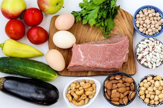 Flexitäre ernährung mit frischem gemüse, rohem fleisch, eiern, hülsenfrüchten, nüssen, obst auf weißer oberfläche, draufsicht