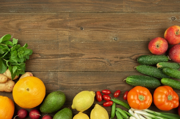 Flexitana-diätkonzept. zusammensetzung mit verschiedenem frischem bio-gemüse und obst. platz für text. gurken, tomaten, rettich, avocado, erbsen, kartoffeln, zitrone, zwiebeln. essen auf dunklem holzhintergrund.