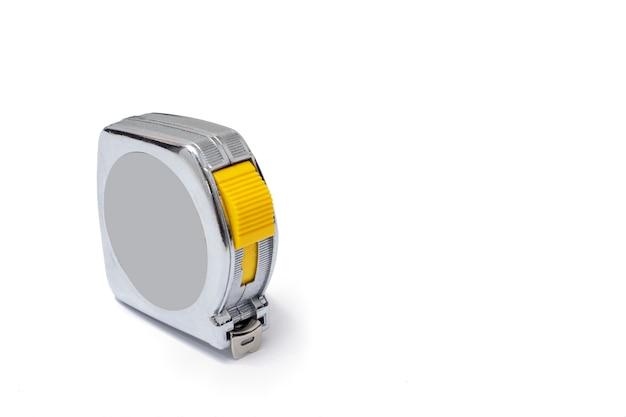 Flexometro plateado con la cinta metrica extendida sobre un fondo de color blanco