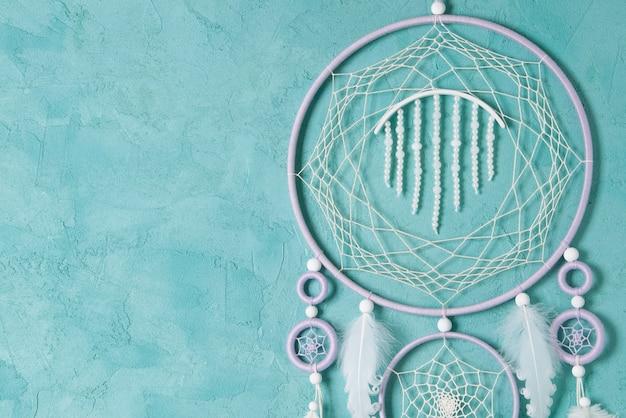 Flieder cremeweißer traumfänger auf aquamarinbetonhintergrund. kopieren sie platz für text.