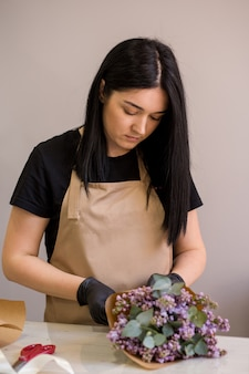 Flieder in den händen eines floristenmädchens, das einen blumenstrauß in einem blumenladen schafft