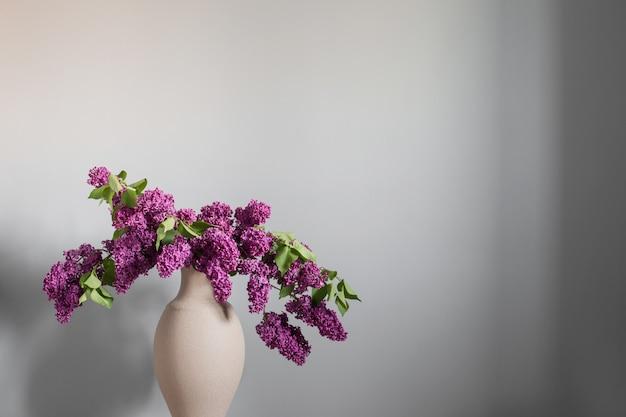 Flieder in vase auf grauem hintergrund