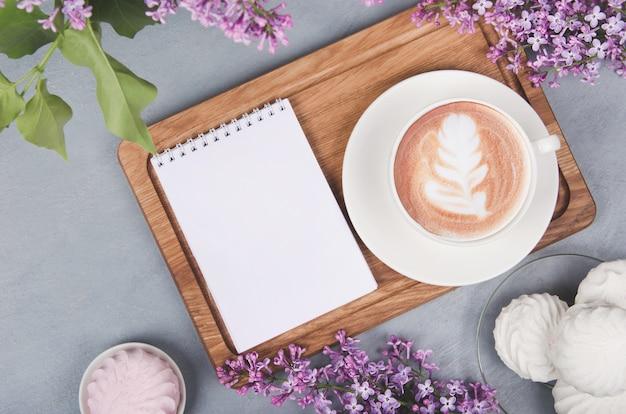 Flieder, kaffeetasse mit latte art und marshmallow auf weißem holztisch. flach liegen