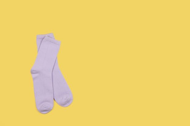 Flieder kindersocken, lokalisiert auf gelbem hintergrund mit kopierraum, flach, minimaler stil. konzept kinderkleidung, haushalt, sortieren, entstören, organisieren.