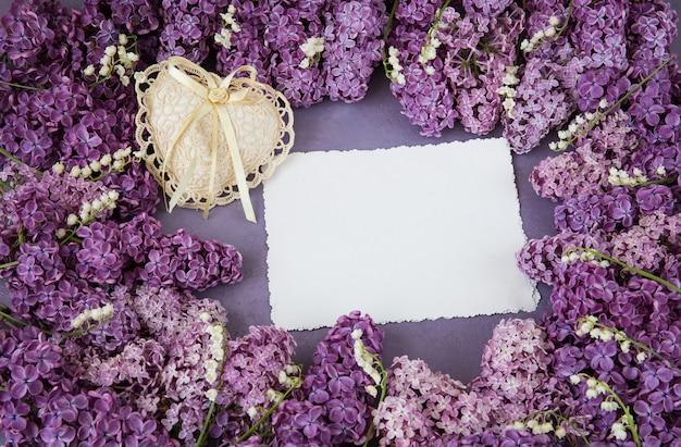 Flieder und maiglöckchen sind mit einem rahmen, einem leeren blatt papier und einem herzen aus spitze gesäumt