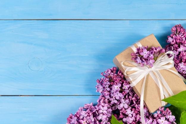 Fliederblumen mit einem geschenk auf einem hellblauen hölzernen hintergrund.
