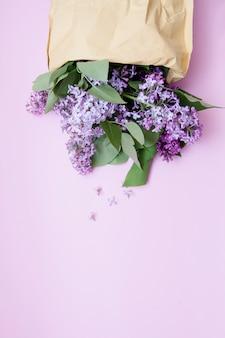 Fliederblumen verschütten aus einer basteltasche auf einem rosa flachen laienhintergrund. draufsicht des frühlingsblumenlayouts