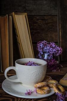 Fliederstrauß und eine weiße tasse tee auf einem hölzernen hintergrund