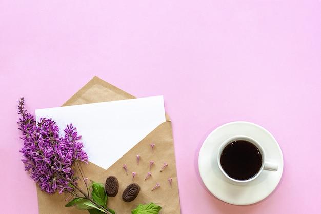 Fliederzweig auf handwerksumschlag mit leerer karte und kaffee
