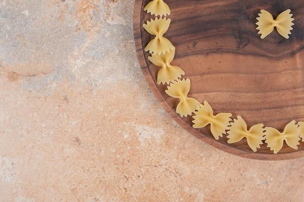 Fliege nudeln auf holzplatte auf marmorplatz.