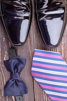Fliege und schwarze schuhe. krawatte und schuhe. bereiten sie sich auf die party vor.