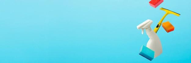 Fliegen im luftschaber, spray und schwämme zum reinigen und waschen auf einem blauen isolierten hintergrund. reinigungskonzept.