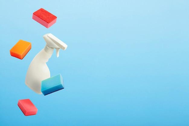 Fliegen in der luft weiße flasche mit spray und schwämmen zum reinigen und waschen auf einem blauen isolierten hintergrund. reinigungskonzept.
