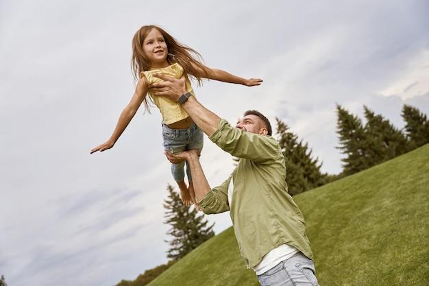 Fliegen mit dem jungen liebevollen vater des papas, der seine süße und glückliche kleine tochter spielt und spaß hat