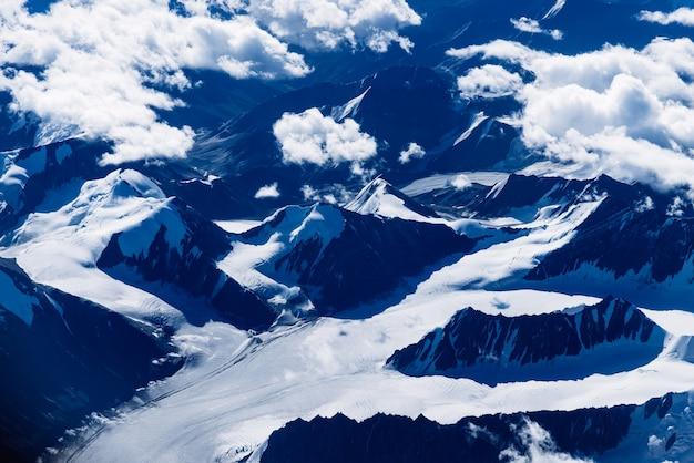 Fliegen über die gefrorene bergkette nach leh in ladakh. luftaufnahme aus dem flugzeugfenster.