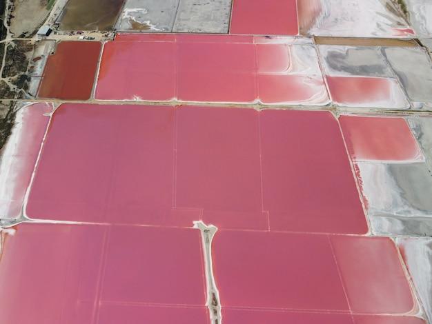 Fliegen über einen rosa salzsee salzproduktionsanlagen salzhaltige verdunstungsteichfelder im salzigen