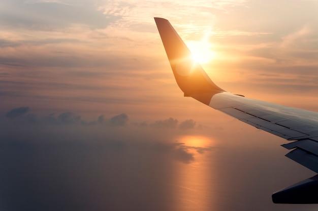 Fliegen und reisen, blick vom flugzeugfenster auf den flügel bei sonnenuntergang.