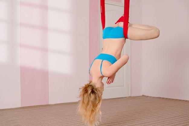Fliegen yoga. das mädchen führt luftyogaübungen durch