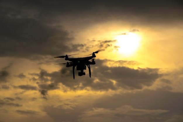 Fliegenbrummen mit kamera auf dem himmel bei sonnenuntergang
