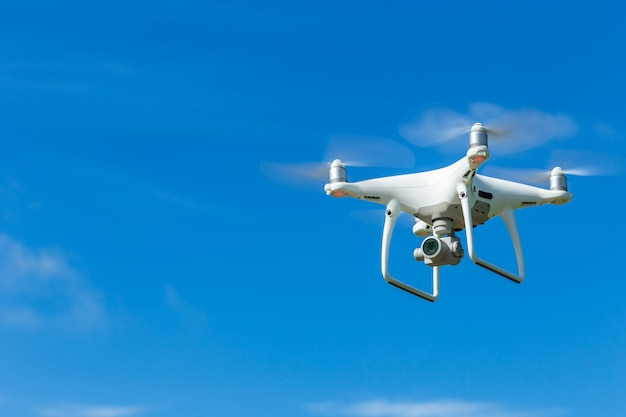 Fliegenbrummen quadcopter mit digitalkamera auf blauem himmel