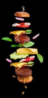 Fliegende burger-zutaten: schnitzel, sesambrötchen, tomate, zwiebel, grüner salat, käse auf schwarzfläche, köstlicher doppel-cheeseburger