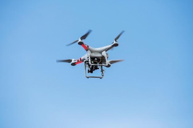 Fliegende drohne mit professionellen kino-kamera am himmel