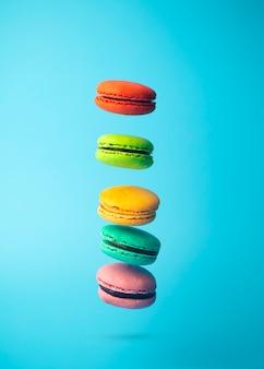 Fliegende farbige makronenplätzchen auf einem blauen hintergrund. helles festliches gebäck, desserts und süßigkeiten. backhintergrund
