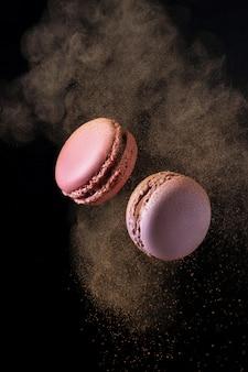 Fliegende französische rosa und lila makronen mit kakaopulver