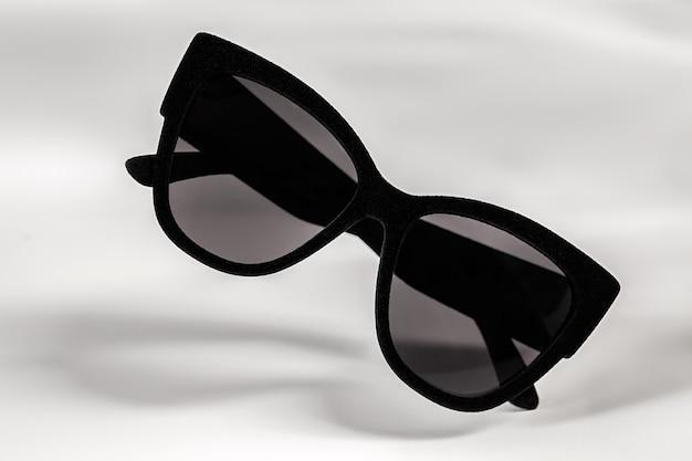 Fliegende frauensonnenbrille in einem wirklich schwarzen rahmen, der mit samt bedeckt ist