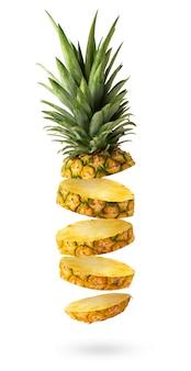 Fliegende frische ananasscheiben isoliert auf weißem hintergrund. kreatives food-konzept.