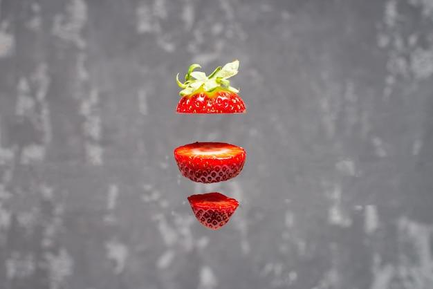 Fliegende frische köstliche reife rote erdbeere, die in scheiben geschnitten auf betonhintergrund geschnitten wird. konzept der lebensmittelschwebung.