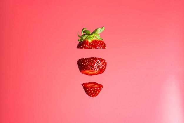 Fliegende frische köstliche reife rote erdbeere, die in scheiben geschnitten wird, die auf rosa hintergrund lokalisiert werden. konzept der lebensmittelschwebung.