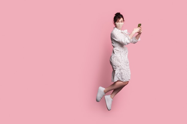Fliegende kaukasische frau in einem kleid, das eine medizinische maske trägt, hält ein telefon und posiert auf einer rosa wand mit freiem raum