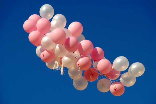 Fliegende luftballons in den blauen himmel