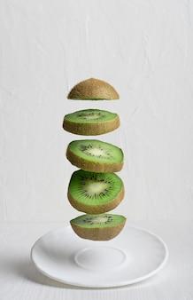 Fliegende reife kiwi-fruchtscheiben über platte gegen weißen hintergrund