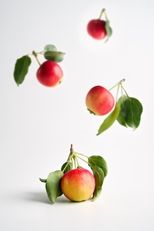 Fliegende rote und gelbe reife äpfel mit blättern auf hellem hintergrund