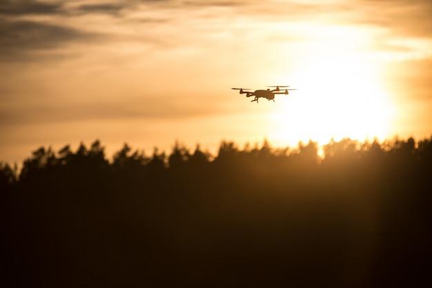 Fliegende silhouette der drohne gegen sonnenuntergang. fliegende silhouette der drohne gegen schönen sonnenuntergangshimmel