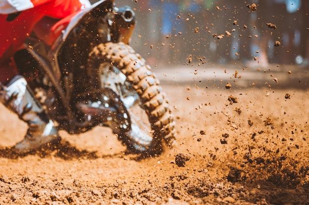 Fliegende trümmer während einer beschleunigung mit mountainbikes auf sandbahn