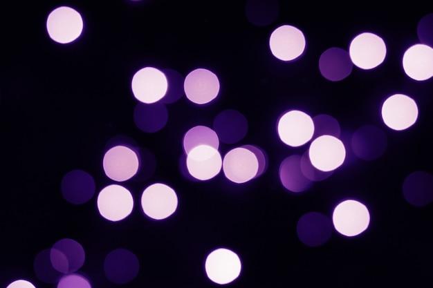 Fliegende violette bokeh-lichter auf schwarz. urlaubskonzept.