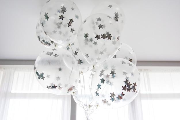 Fliegende weiße luftballons mit silbernen sternen unter der decke