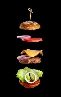 Fliegende zutaten eines klassischen cheeseburger: sesambrötchen, zwiebelringe, tomatenscheiben