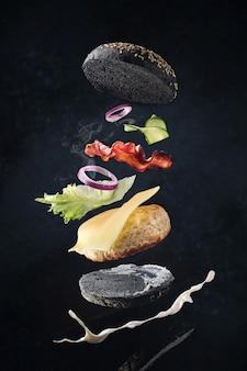 Fliegender burger mit speck und hühnerschnitzel zwischen einem schwarzen brötchen.