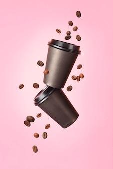 Fliegender kaffee von einem pappbecher mit fliegenden kaffeebohnen auf einem rosa hintergrund. kaffeekonzept. attrappe, lehrmodell, simulation. leere polystyrol-kaffee-trinkbecher-modell-vorderansicht. klares einfaches tee zum mitnehmen.