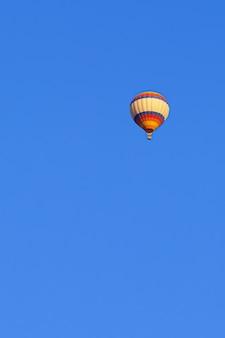 Fliegender mehrfarbiger ballon im strahlend blauen himmel