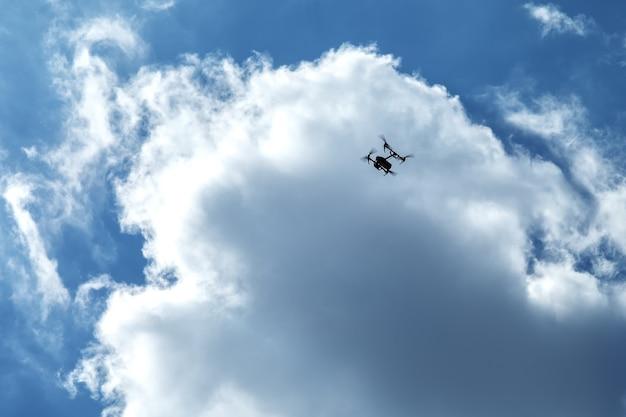 Fliegender quadrocopter auf wolken und blauem himmel